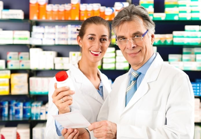 two pharmacists with a bottle of veterinarian compounded medication